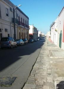 Alezio, via Garibaldi In questa strada oltre il segnale triangolare, c'era l'abitazione di mia nonna con accesso diretto dalla strada e giardino sul retro. Alla fine della strada si intravede l'edificio della piccola stazione ferroviaria.